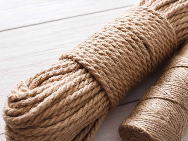 Natural jute twine roll on white wood background. Supplies and tools for handmade hobby leisure closeup