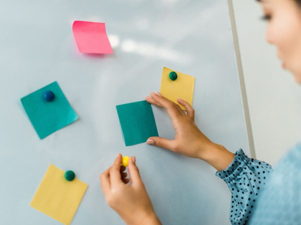 cropped view of woman putting colorful sticky notes on white board in office