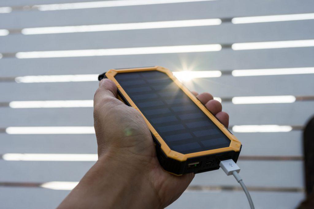 Mano sosteniendo power bank solar