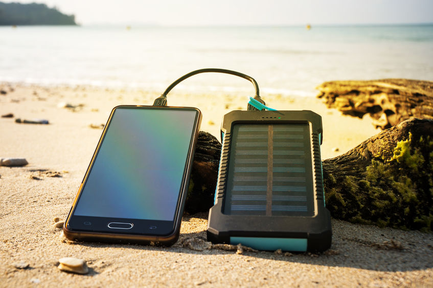 Power bank solar cargando celular en la playa