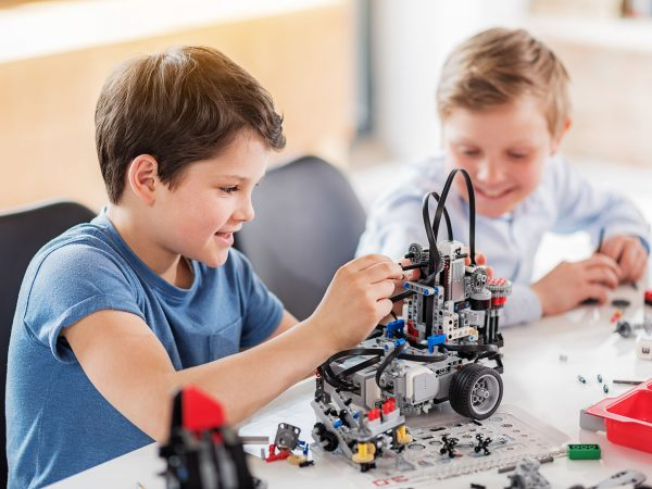 Interested male child is making robot, his friend looking at it with smile. They sitting near desk. Portrait