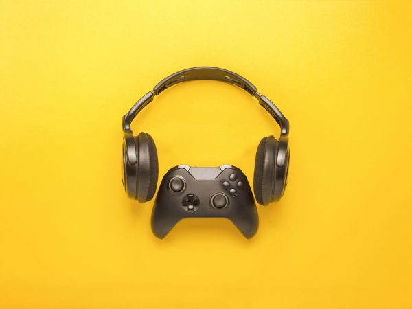 Black headphones and a gamepad on yellow background. Concept of the game on the console or computer. Rest after work. Cybersport. Flat lay, top view.