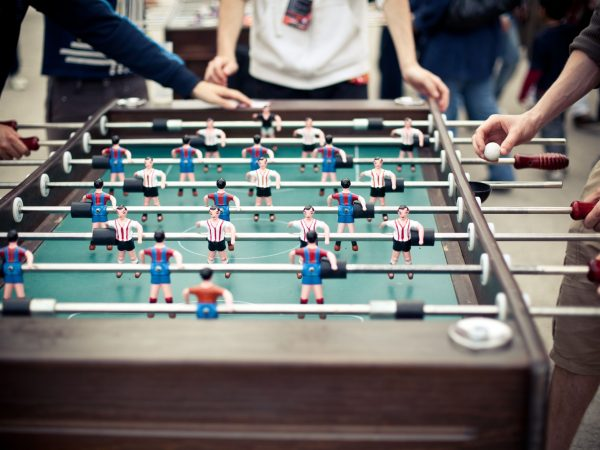 10697198 – outdoor green table football board with many colorful figures and a few players around