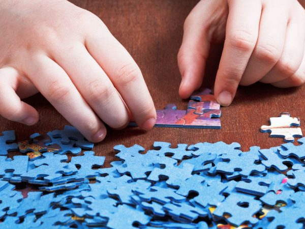 attaching of jigsaw puzzles on wooden table