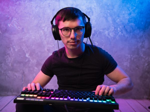 Portrait of the young handsome pro gamer sitting on the floor with keyboard in neon colored room.