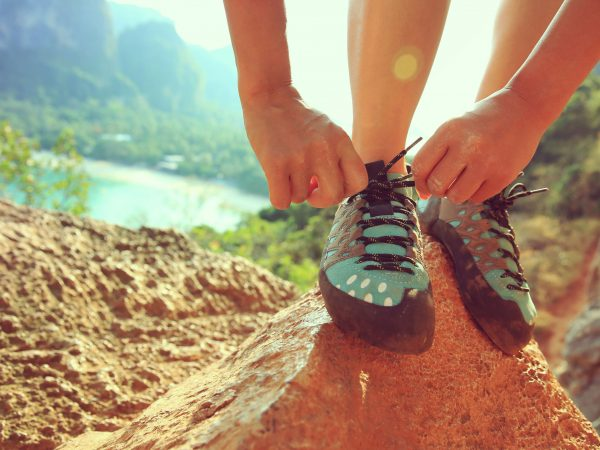 one young woman rock climber tying shoelace on rock