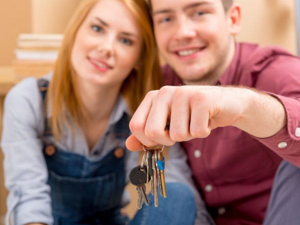 Happy couple celebrating their new home, keys in hand.