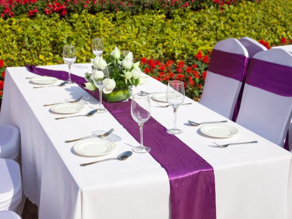 15162036 – outdoor tables with served plates and wine glasses in the garden