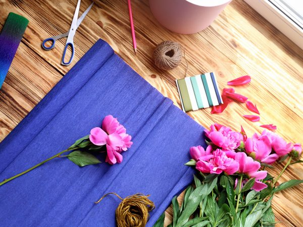 Workplace of florist with fresh peonies and wrapping paper on wooden table