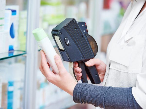 Hand of female pharmacist using labeling gun labeler for sticking price label of medicine in in drugstore
