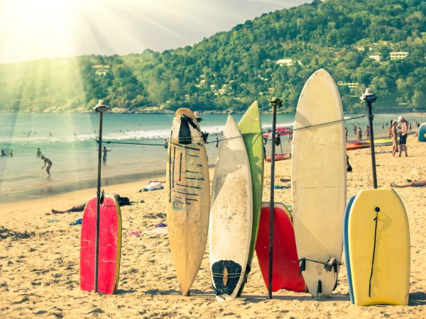 Multicolored surfboards at  Kata Beach in Phuket Island – Surf boards at tropical exclusive destination in south east Asia – Wonders of Thailand on vintage filtered look with enhanced sunshine