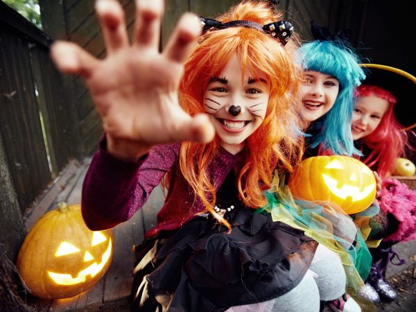 Halloween girl looking at camera with her hand in frightening gesture