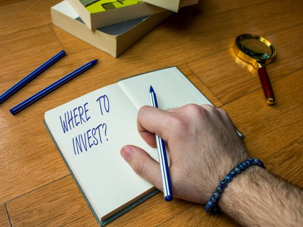 Word writing text Where To Invest Question. Business photo showcasing asking about where put money into financial schemes or shares Close up view man writing notebook pen set lying wooden table two books
