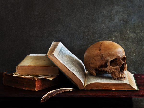still life art photography on human skull skeleton with book omn desk