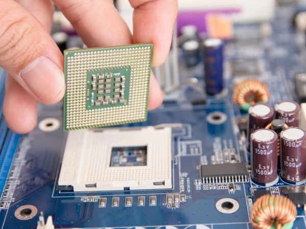 Technician installing CPU chip microprocessor to socket on motherboard