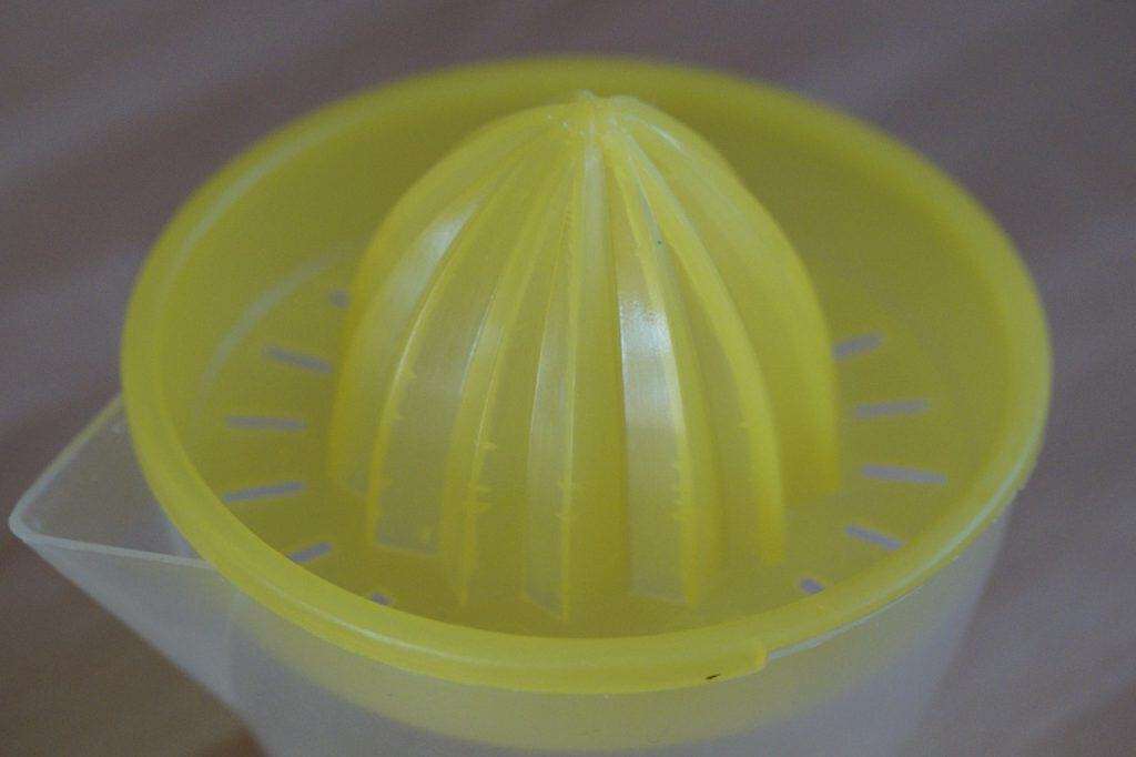 Espremedor de laranja, feito de plástico, com a peneira na cor amarela.