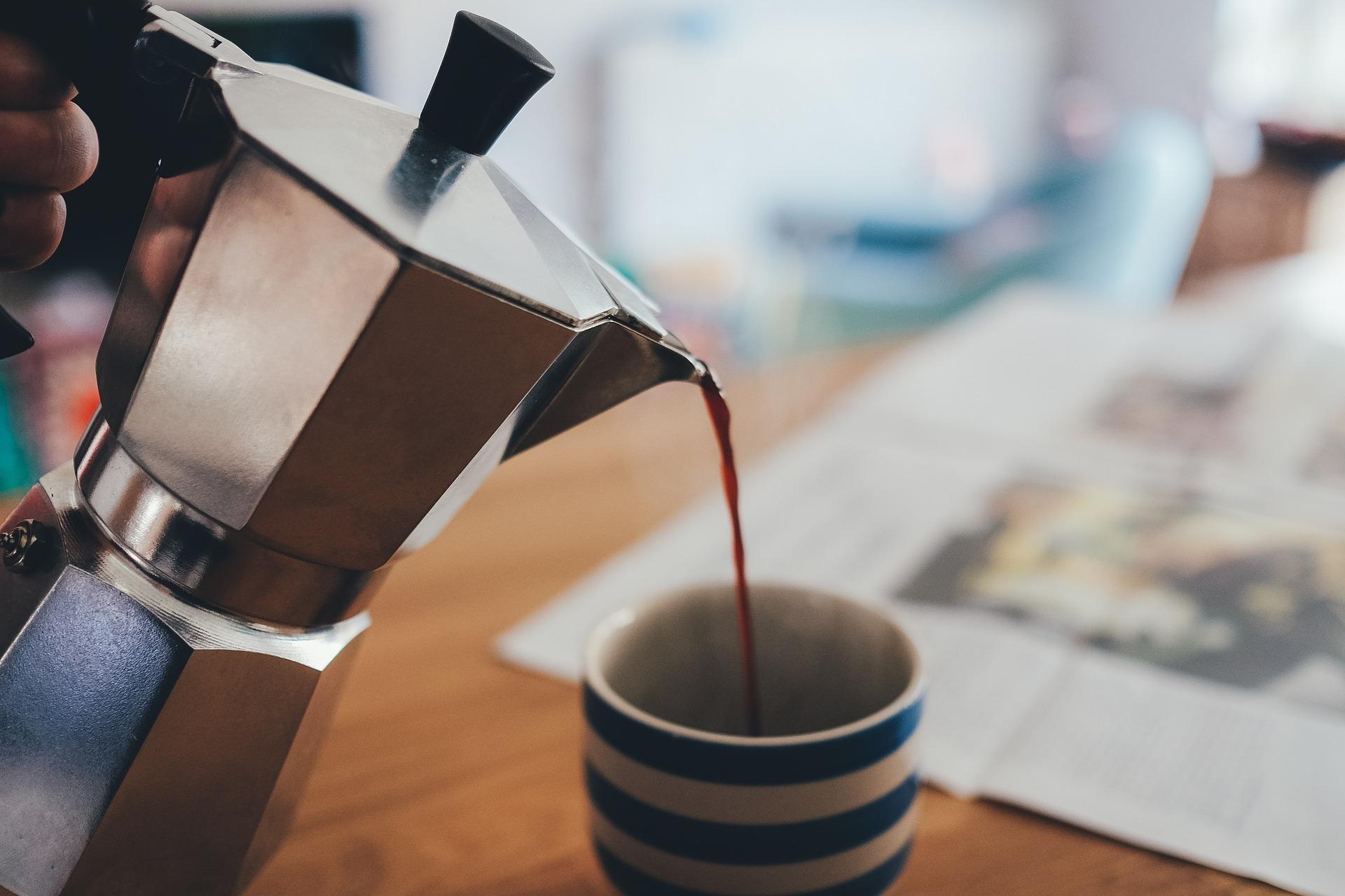 Na foto uma pessoa colocando café em um xícara segurando uma cafeteira italiana.