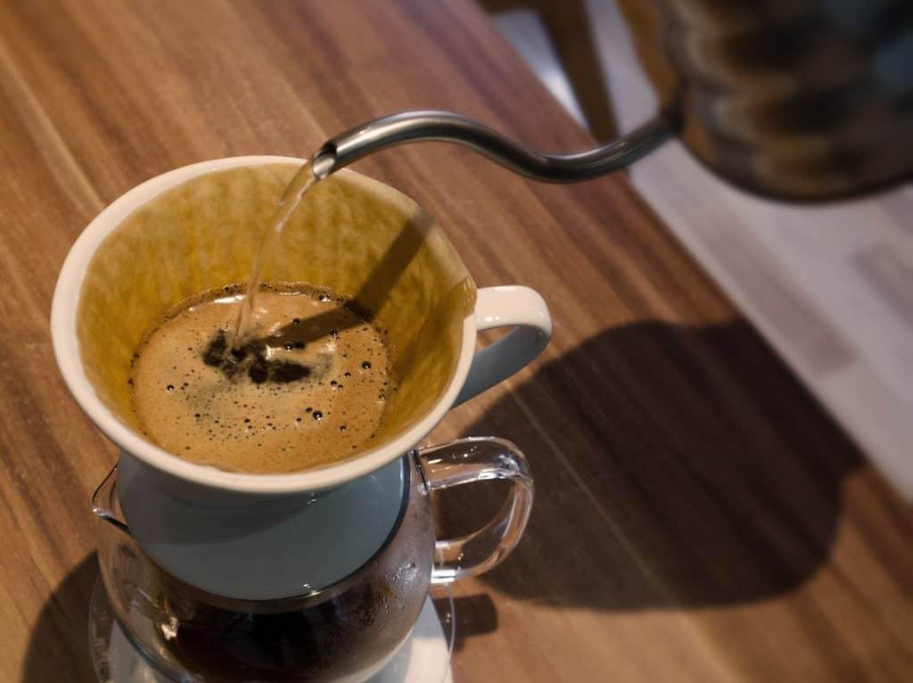 Café sendo coado em filtro de papel e suporte de cerâmica.