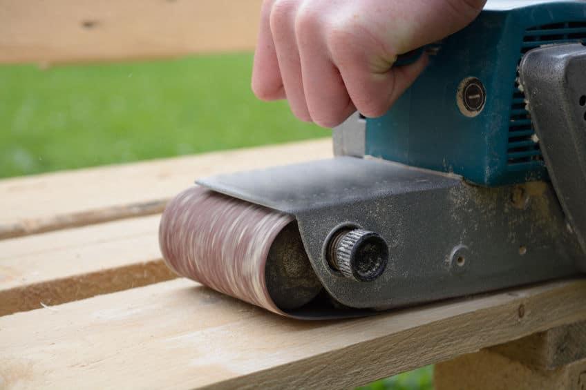 Mão segurando uma lixadeira de cinta em funcionamento sobre uma tábua de madeira.