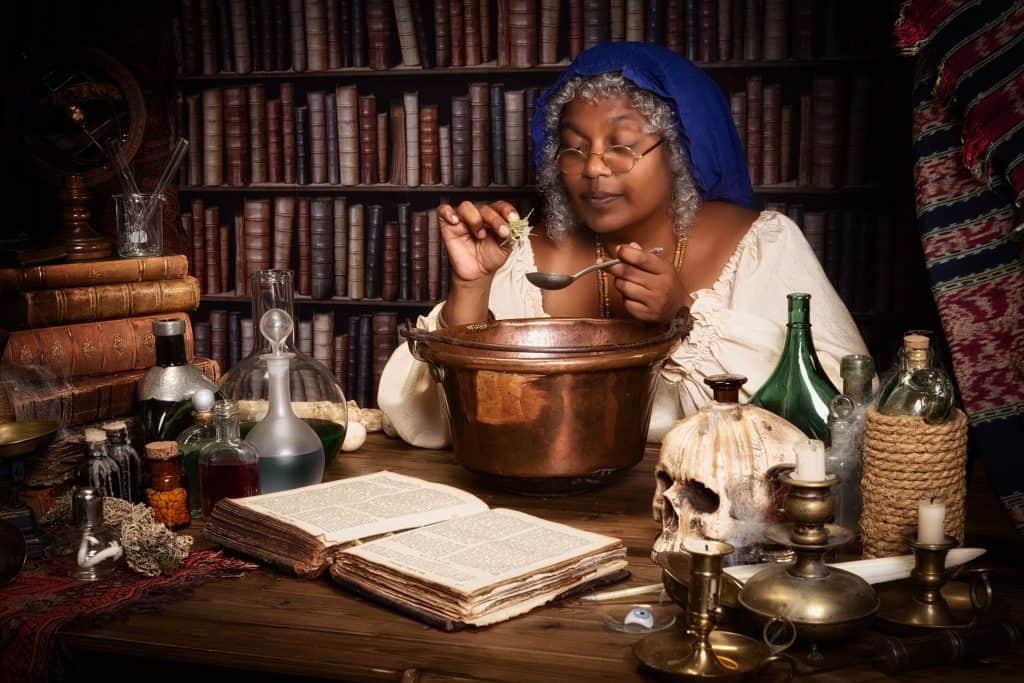 Uma mulher com cabelos grisalhos fazendo uma poção em uma biblioteca.