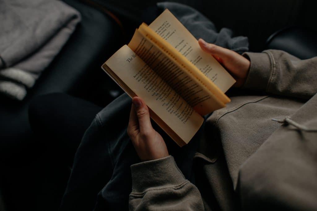 Imagem retrata uma pessoa a partir apenas de seu tronco. Ela folheia um livro, segurando-o na altura do seu colo.