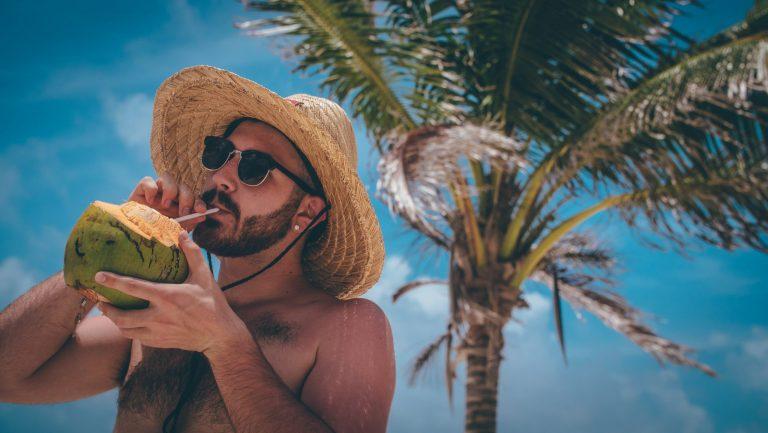Na foto um homem tomando água de coco embaixo de um coqueiro.