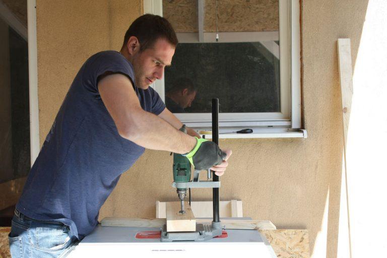 Imagem mostra um homem trabalhando com uma furadeira em madeira.