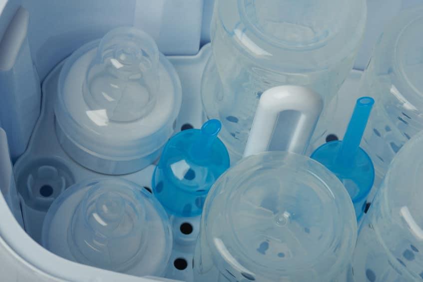 Um esterilizador de mamadeira aberto com mamadeiras dentro.