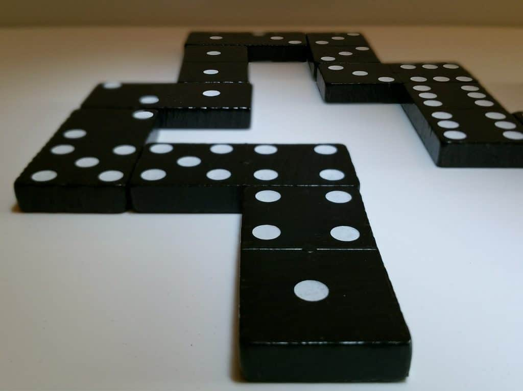 Imagem mostra a combinação de peças de dominó em cima de uma superfície branca.