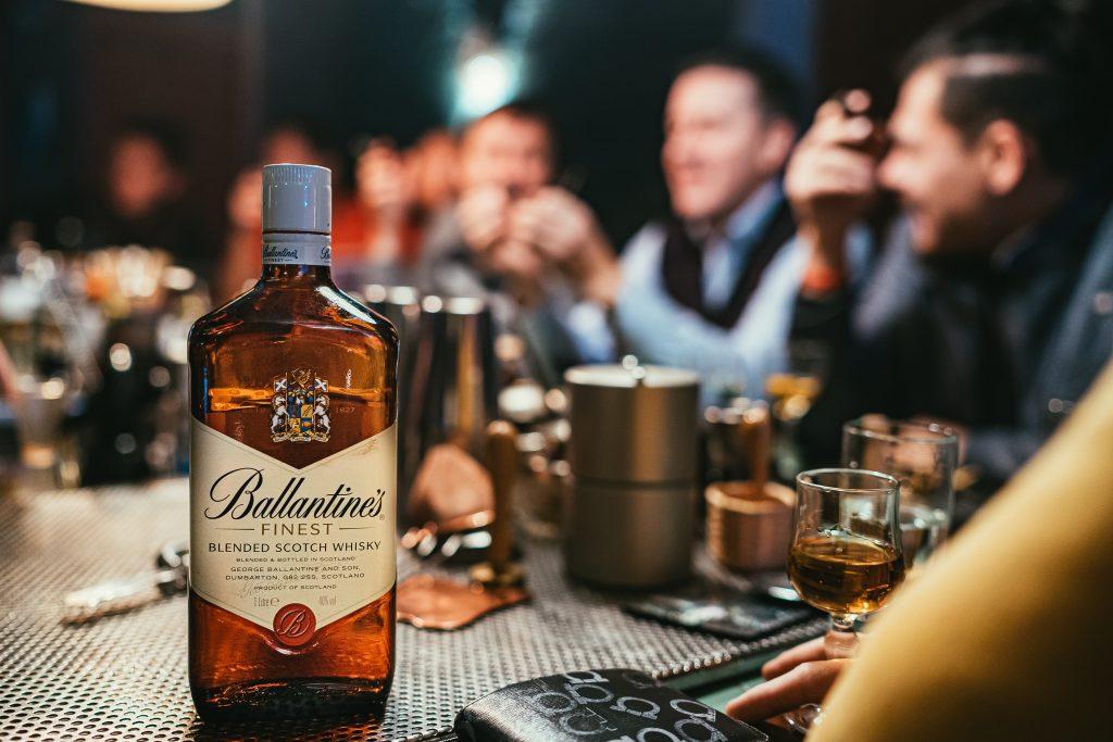 homens em uma mesa com whisky em destaque