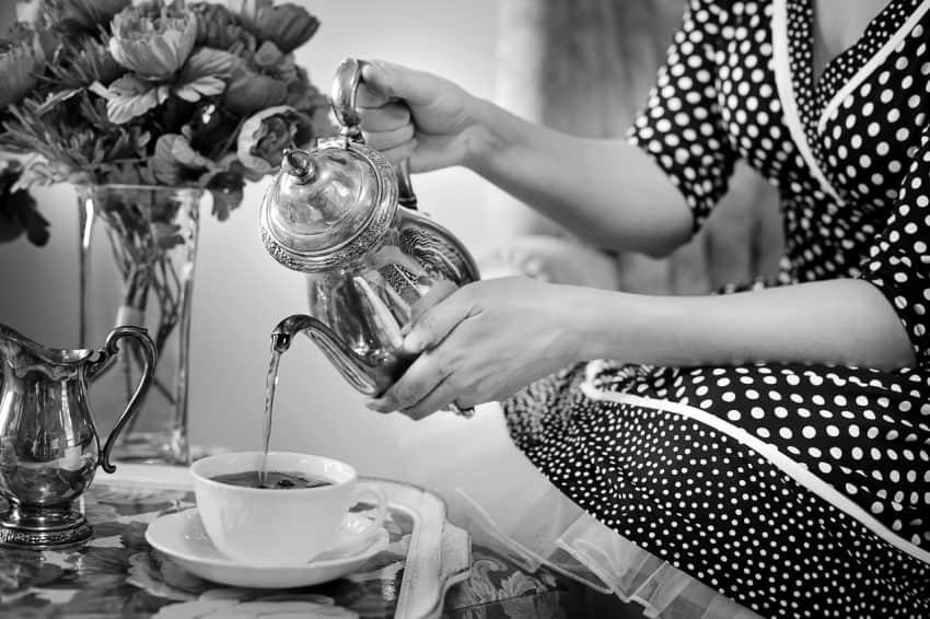 Foto antiga em preto e branco de mulher agachada servindo café em mesa de centro, ela segura um bule de prata.