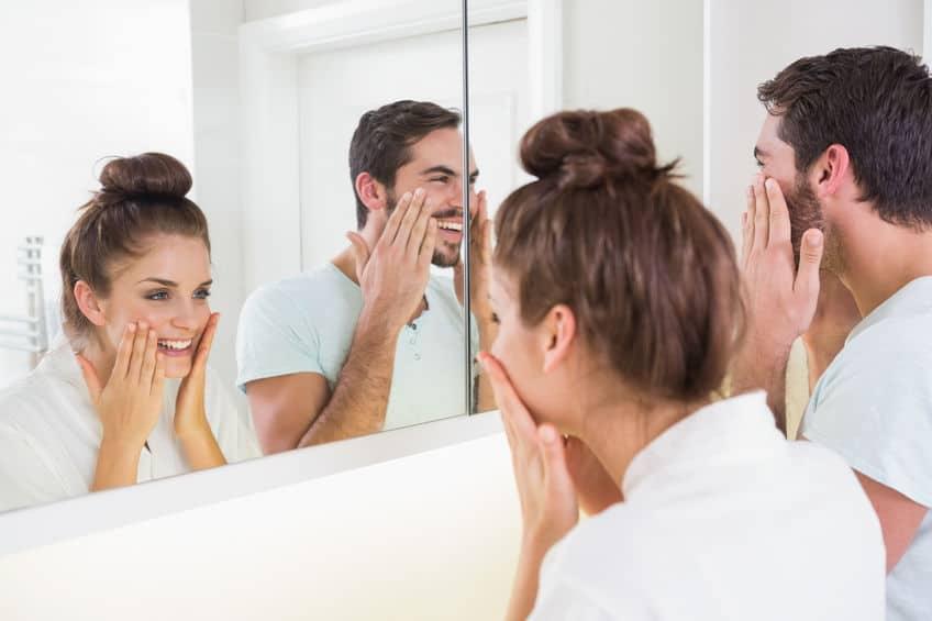 Casal se olhando em espelho de banheiro.