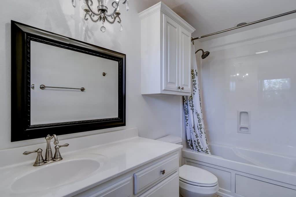 Imagem de banheiro com espelho com moldura de madeira.