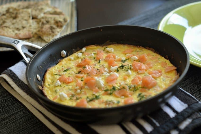 Omelete com pedaços de salmão preparado em frigideira.