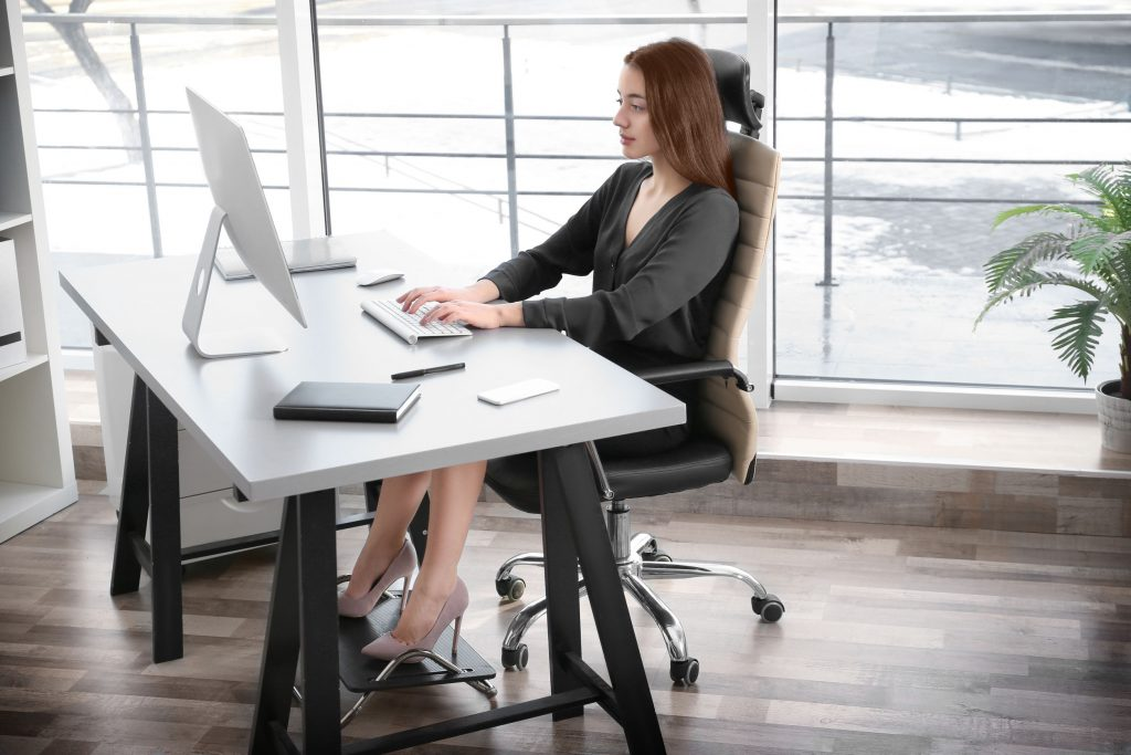 Uma mulher jovem sentada em sua mesa no escritório usando um descanso de pés.