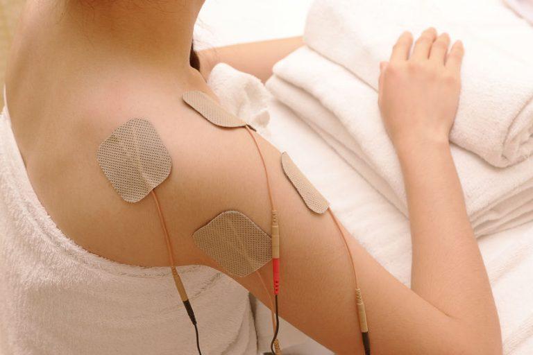 Imagem de una mulher com um eletroestimulador nas costas.