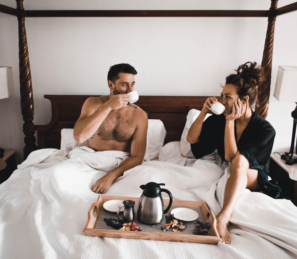 Imagem de um casal tomando café da manhã na cama