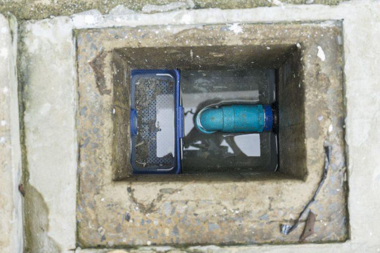 Na foto uma caixa de gordura de alvenaria com água dentro.