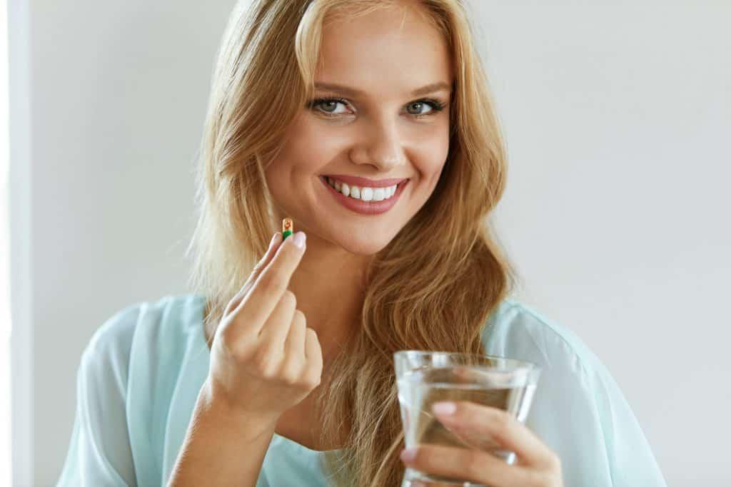 Imagem de uma mulher tomando uma pílula.