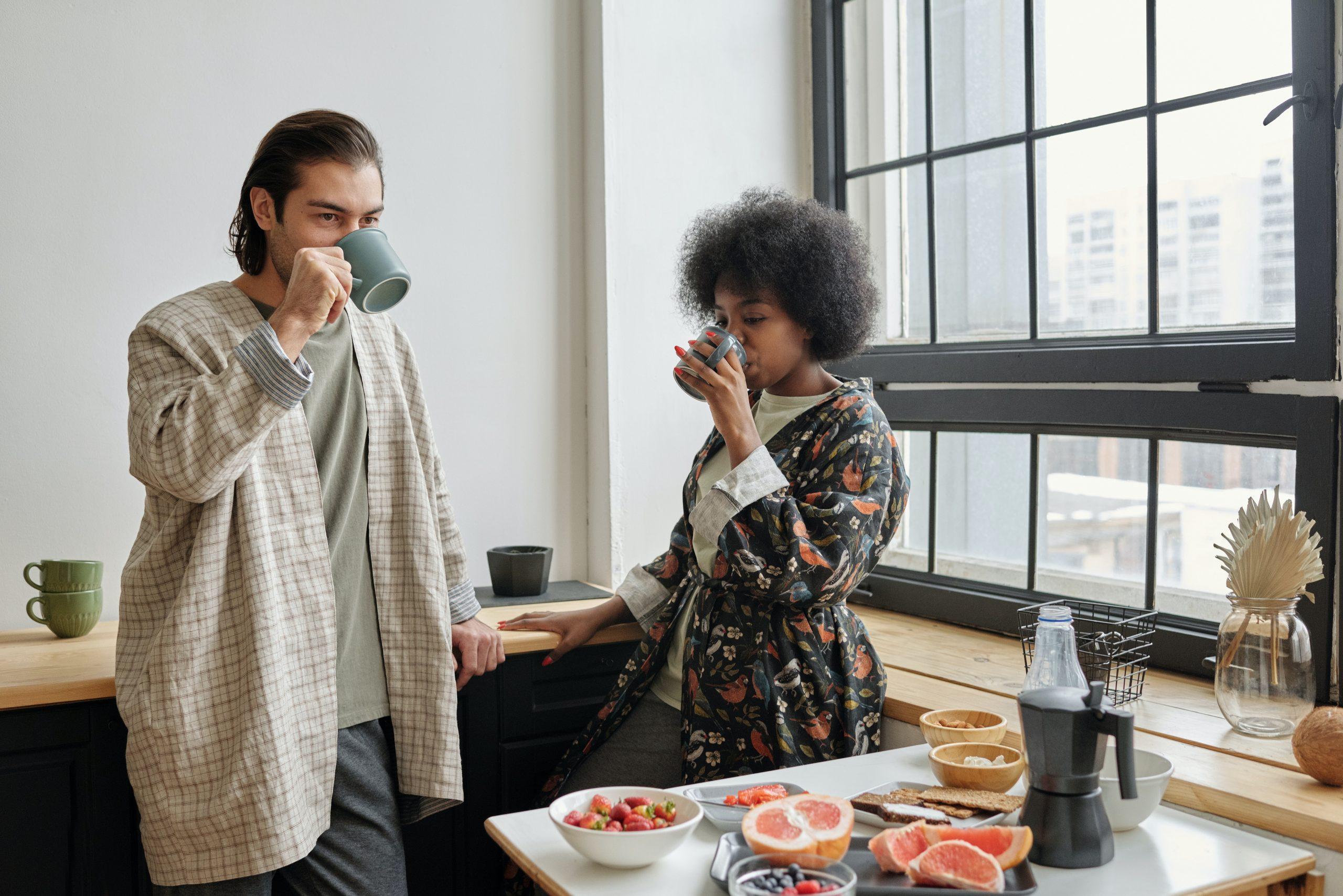 Na foto um homem e uma mulher em pé em uma cozinha tomando café ao lado de uma mesa com alimentos de café da manhã.