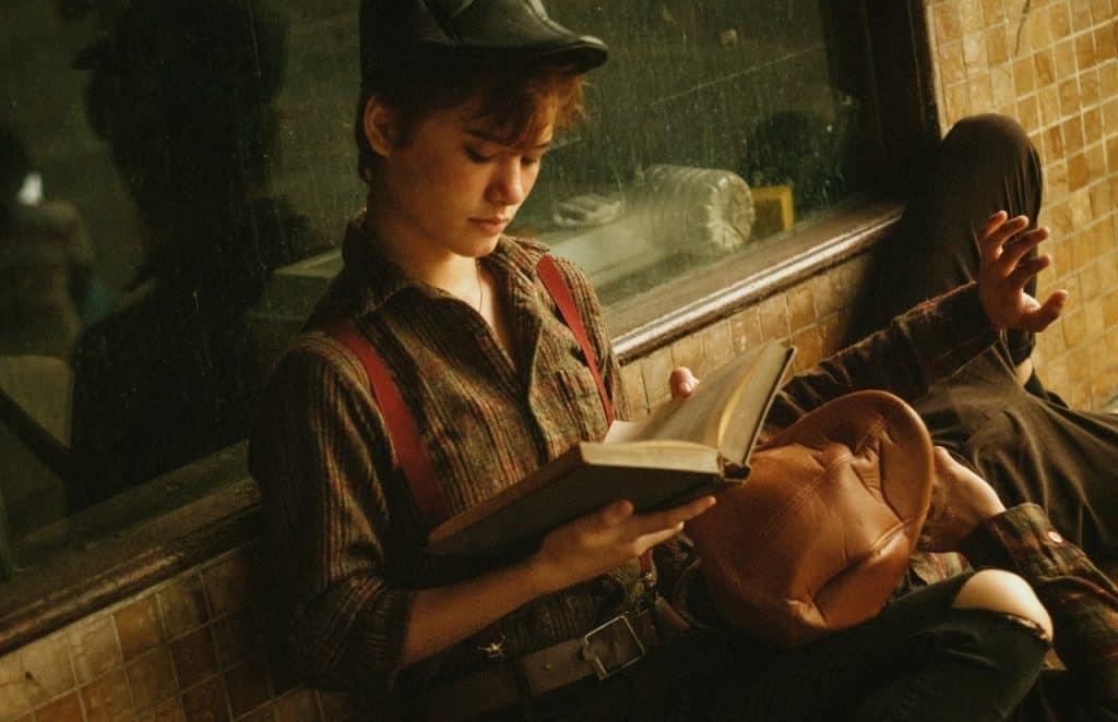 Um homem está deitado no colo de uma mulher que, por sua vez, está sentada lendo um livro.