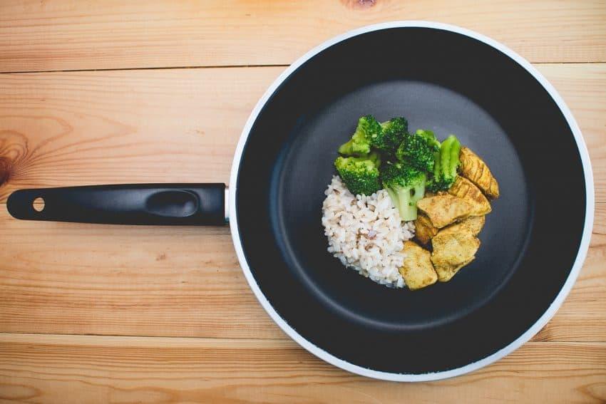 Frigideira vista de cima com arroz, frango e brócolis.