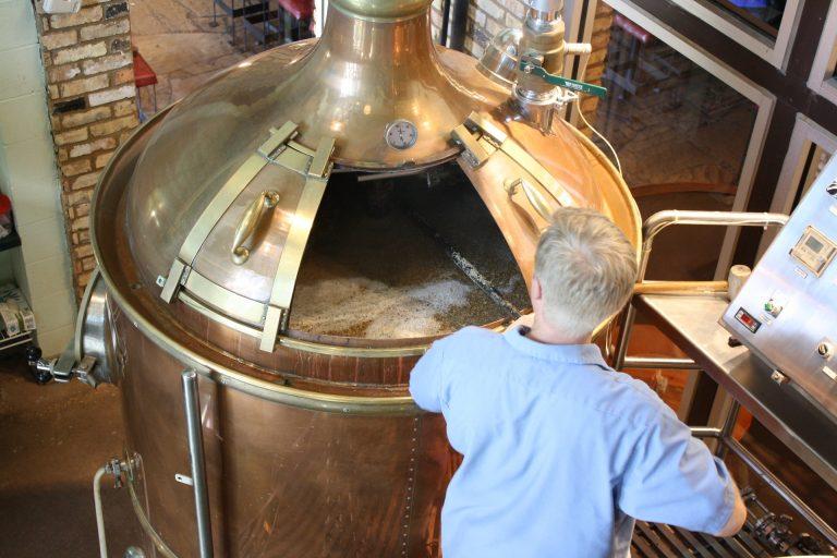 Um homem grisalho na frente de um fermentador grande de metal com cerveja até a borda.