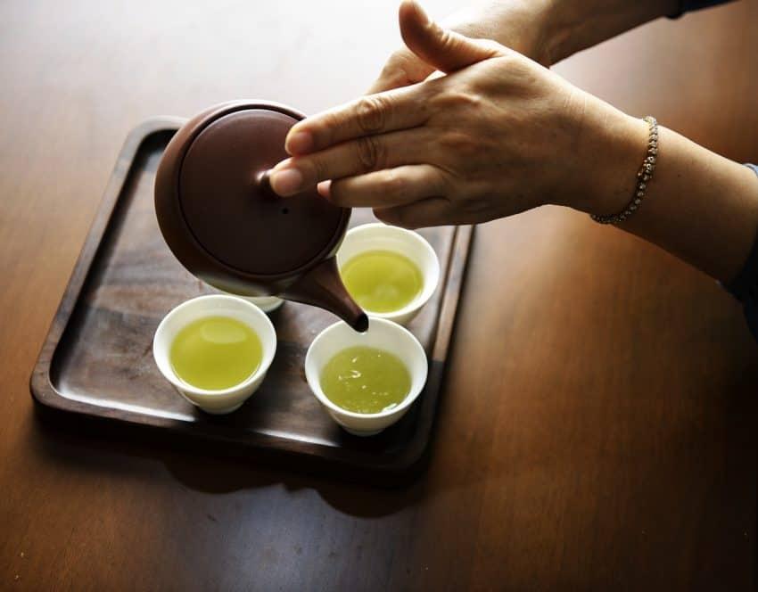 Imagem mostra as mãos de uma mulher servindo chá numa bandeja com pequenas xícaras com um bule de cerâmica.