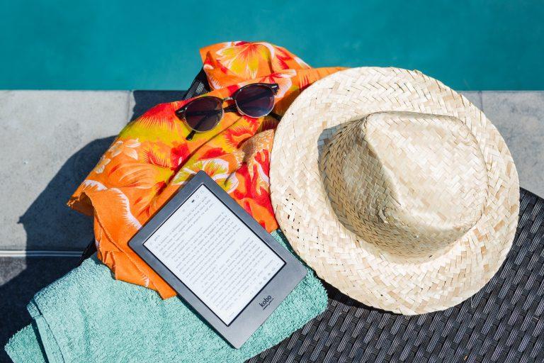 Foto de um chápeu de praia junto de um kindle, uma canga, uma toalha e um óculos de sol, ao lado de uma piscina.