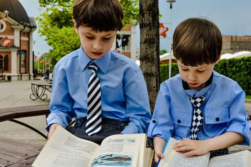 Duas crianças, cada uma está com um livro aberto. Elas estão sentadas em um banco de praça com arquitetura de Londres.