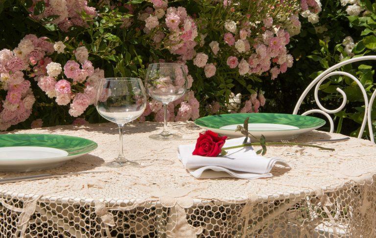 Mesa ao ar livre próxima a roseira com toalha em renda Legenda: Toalhas de mesa rendadas são sinônimo de leveza e sofisticação