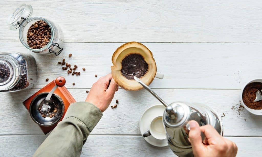 Pessoa preparando café, com xícara ao lado e cafés.