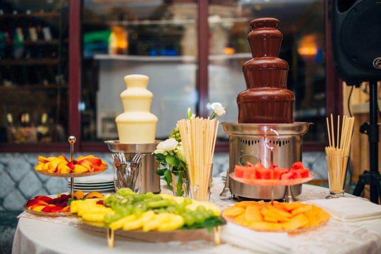 Na foto uma mesa com duas fontes de chocolate e bandejas com frutas.