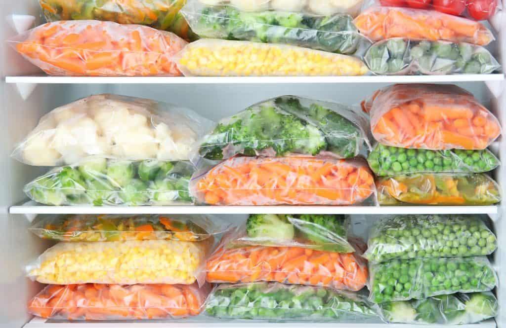 Imagem mostra vegetais em sacos dentro de freezer.